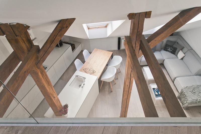 Drewniane okna FAKRO idealnie komponują się z belkami konstrukcyjnymi oddzielającymi kuchnię od przestrzeni wypoczynkowej na poddaszu. Fot. Fakro
