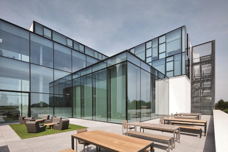 Ogromne transparentne przeszklenia nowoczesnego budynku Experience Centre otwierają wysoki na dwie kondygnacje hol wejściowy na zewnętrzną przestrzeń i wprowadzają światło do wnętrz. Fot. Reynaers